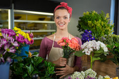 Female florist holding bunch of flower in flower shop Stock Image