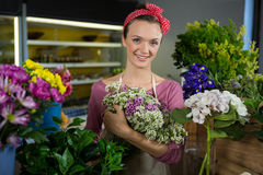 Female florist holding bunch of flower in flower shop Stock Photos