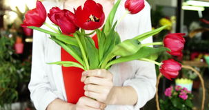 Female florist holding bunch of red flower in flower shop. Slow motion of female florist holding bunch of red flower in flower shop stock video footage