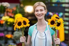Female florist holding flowers in flower shop Stock Image
