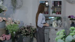 Female florist inspecting flowers at her flower shop stock video