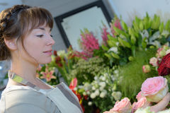 Female florist looking pink rose in flower shop Royalty Free Stock Photography