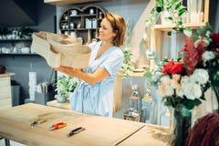Female florist makes flower composition in shop stock images