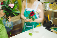 Female florist making beautiful bouquet at flower shop Stock Images