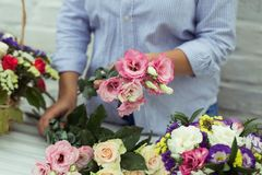 Female florist making beautiful bouquet at flower shop.  royalty free stock image