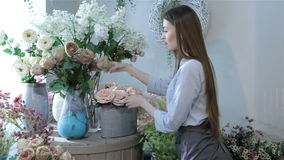 Female florist moving flowers near the window at flower shop stock video