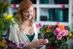 Female florist preparing flower bouquet Stock Photos
