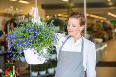 Female Florist Smelling Purple Flowers In Shop Royalty Free Stock Images