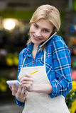 Female florist taking order on mobile phone in flower shop Royalty Free Stock Image