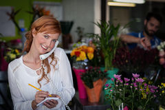 Female florist taking an order on telephone Royalty Free Stock Photography