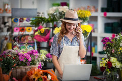 Female florist talking on mobile phone while using laptop Stock Images