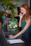 Female florist talking on mobile phone while using laptop Royalty Free Stock Images