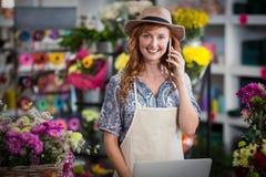 Female florist talking on mobile phone while using laptop Stock Image
