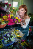 Female florist touching flower bouquet Royalty Free Stock Photos