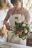 Female florist trimming a flower arrangement in her shop royalty free stock image