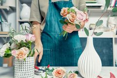 Female florist unfocused in flower shop making beautiful artificial bouquet. A teacher of floristry in master classes or courses. Professional, floral stock photos
