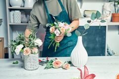 Female florist unfocused in flower shop making beautiful artificial bouquet. A teacher of floristry in master classes or courses. stock photography