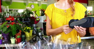 Female florist using credit card terminal. In flower shop stock video footage