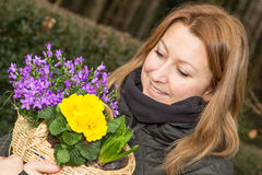 Female with flower basket. Attractive female holding a basket with flowers Stock Image