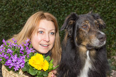 Female with flower basket and dog. Looking at something Stock Photo