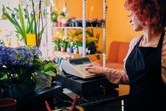 Female flower seller using cash register in a market shop. Redhead female flower seller using cash register in a market shop royalty free stock images