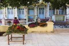 Female flower vendor waiting for customers in Thanboddhay temple complex courtyard stock photos