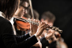 Female flutist with orchestra on stage Royalty Free Stock Photo