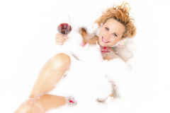 Female in Foamy Bathtub Filled with Petals. Holding a Glass of Red Wine Stock Images