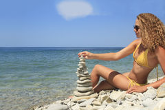 Female folds from stones zen pyramid Stock Photography