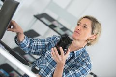 Female food photographer checking photos in camera. Female royalty free stock images