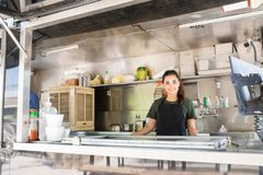 Female food truck owner. Attractive young brunette standing inside her own food truck and looking ready to cook some food royalty free stock image