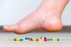Female foot above colored pushpin Royalty Free Stock Image