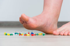 Female foot above colored pushpin Stock Photography