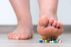 Female foot above colored pushpin. Women feet Royalty Free Stock Photo