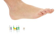 Female foot above pushpin Royalty Free Stock Photography