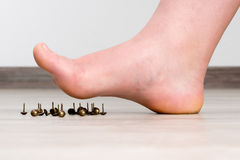 Female foot above pushpin Stock Images