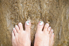 Female Foot with Beautiful Pedicure on the sand. Moving Sea Wate Royalty Free Stock Images