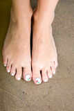 Female Foot with Beautiful Pedicure on the sand. Royalty Free Stock Photo