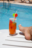 Female foot in front of the pool with drink on a d. Female foot in front of the pool with orange drink on a deck chair Royalty Free Stock Images