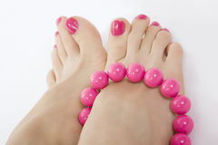 Female foot with pink pedicure and accessory Royalty Free Stock Photo