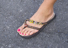 Female foot with sandal with beads. Female foot with sandal with colorful beads Stock Photos