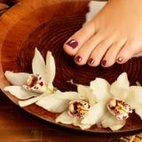 Female foot at spa salon on pedicure procedure. Closeup photo of a female foot at spa salon on pedicure procedure - Soft focus image Royalty Free Stock Photos