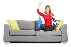 Female football fan cheering seated on a couch. Isolated on white background stock image