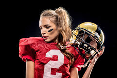 Female football player posing with helmet. Attractive female american football player in uniform posing with helmet on black Royalty Free Stock Images