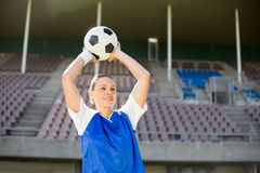 Female football player about to throw a football. In stadium stock images