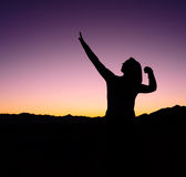 Female Football Win Silhouette. Woman against a sunset in the mountains with her arms raised up in a football stance stock image