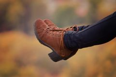 Female foots in brown shoes on a blurred autumn background. Close-up Stock Photos