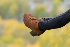 Female foots in brown shoes on a blurred autumn background. Clos. E-up Stock Images