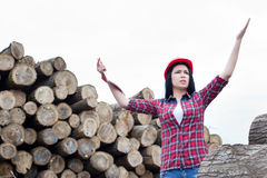 Female forest engineer beside logs Royalty Free Stock Photos