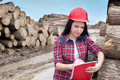 Female forest engineer beside logs Stock Photos